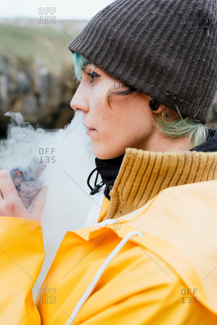 Side view of relaxed female in outerwear smoking vape and exhaling cloud of smoke while standing on Cobijero Beach and looking away