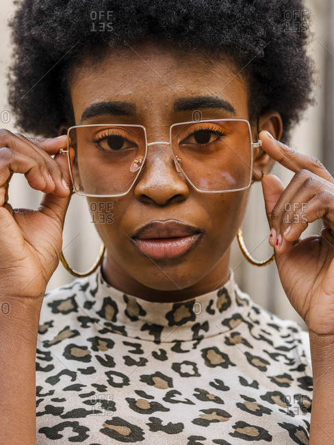 Confident stylish young African American female with curly hair dressed in jeans and crop top with animal print n casual outfit and trendy sunglasses looking at camera while standing on urban street