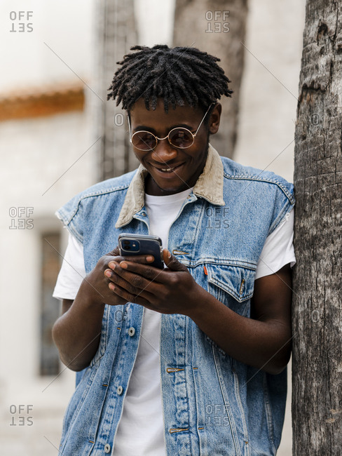 Positive young hipster African American guy with dreadlocks and eyeglasses wearing trendy denim outfit leaning back on tree trunk and browsing smartphone while resting in park