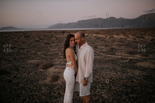 Side view of peaceful couple in white outfit standing together in savanna and looking at camera