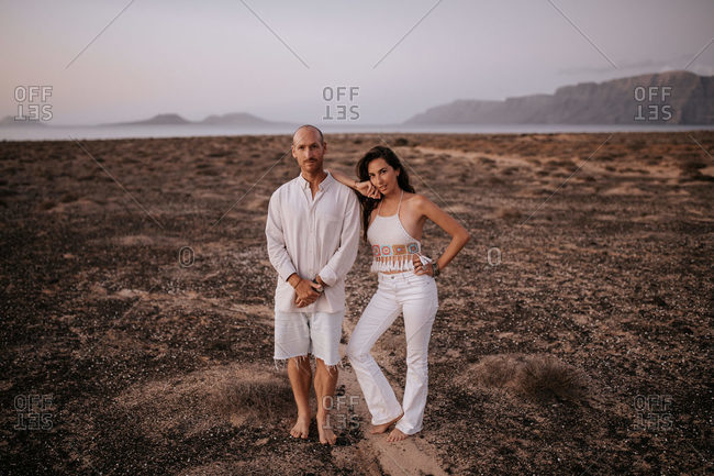 Peaceful couple in white outfit standing together in savanna and looking at camera