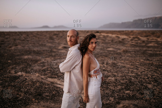 Side view of peaceful couple in white outfit standing back to back in savanna and looking at camera