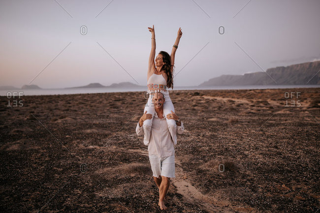 Cheerful woman with raised arms sitting on shoulders of smiling man walking along savanna in evening