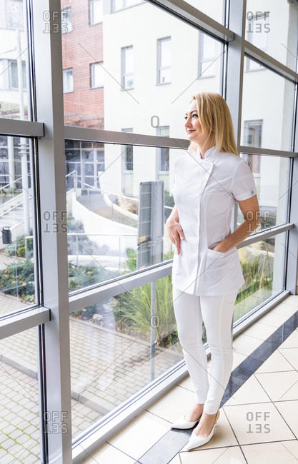 Smiling female medic wearing white uniform standing with hands in pockets in hallway of hospital and looking out of window