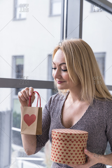 Smiling curious female standing near window with Christmas gifts in craft paper bag and box
