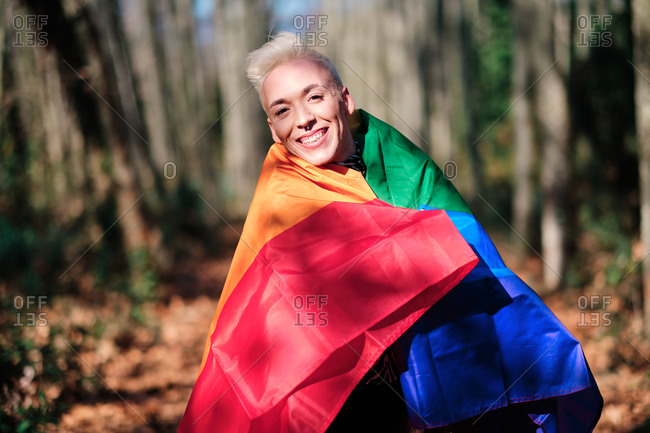 Smiling fashionable young transgender male wrapped on rainbow LGBT flag while standing in sunny forest