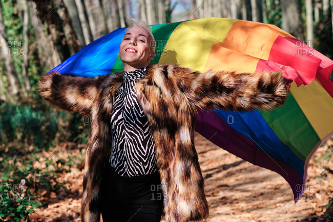 Smiling fashionable young transgender male in fur coat holding rainbow LGBT flag while standing in sunny forest