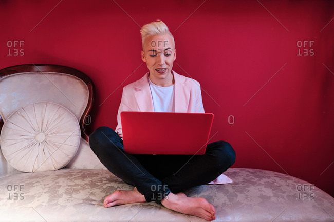 Stylish focused young blond haired transgender male using red laptop while sitting in room with feminine pink colored interior at home