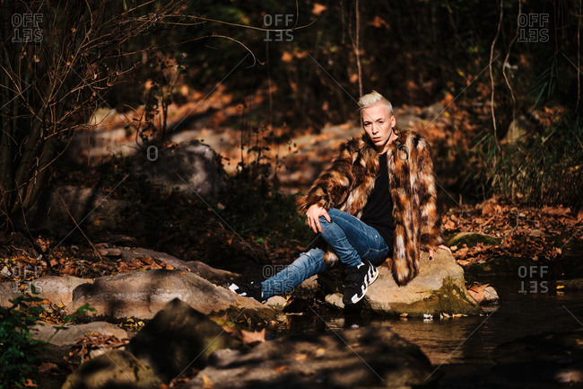 Full body of young blond haired transgender male model in skinny jeans and stylish fur coat sitting on stone near lake in sunny autumn forest