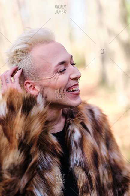 Confident cheerful young blond haired transgender male with makeup wearing stylish fur coat looking at camera while standing in sunny autumn forest