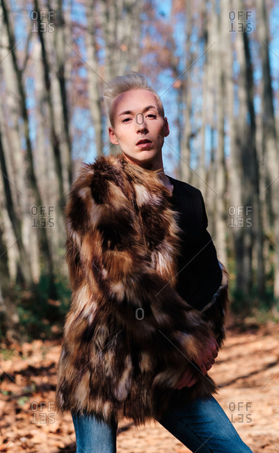 Confident young blond haired transgender male with makeup wearing stylish fur coat looking at camera while standing in sunny autumn forest