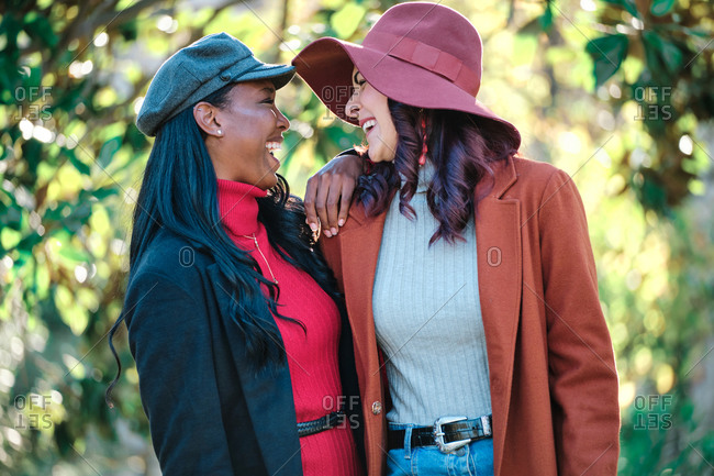 Positive multiethnic female friends in stylish autumn outfits enjoying stroll in park while laughing and having fun at weekend