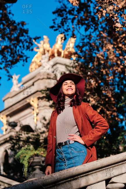 Low angle of delighted female wearing trendy autumn hat standing on stone stairs in park on background of ancient building and looking away