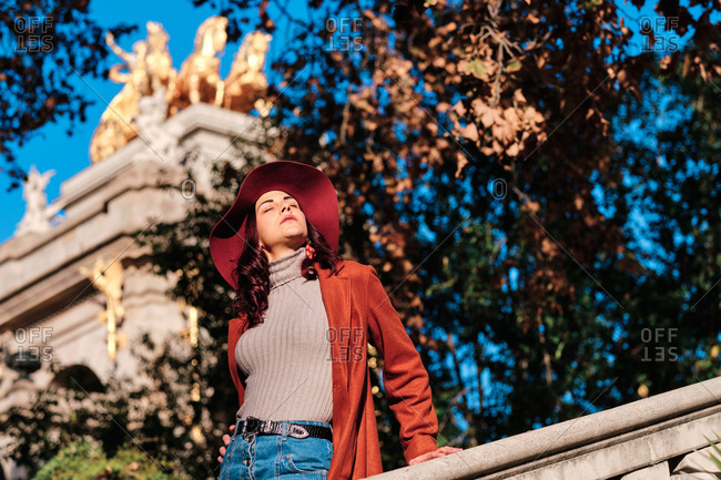 Low angle of delighted female wearing trendy autumn hat standing on stone stairs in park on background of ancient building and closed eyes