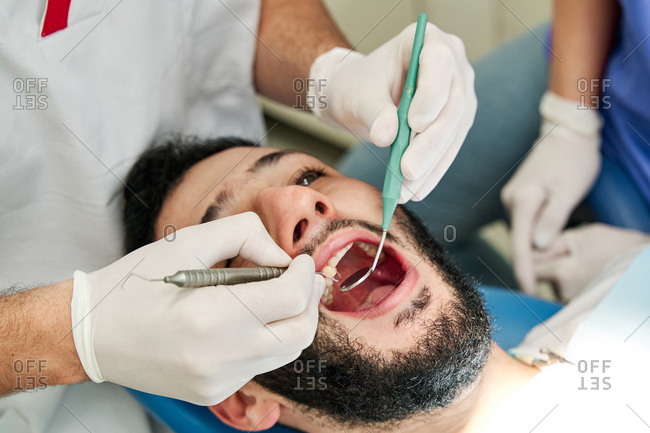 From above of unrecognizable dentist with explorer and dental mirror checking teeth of patient during appointment in modern clinic