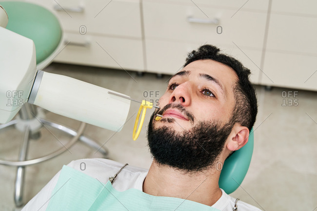 From above of male patient lying in medical chair during dental procedure with professional machine in modern clinic