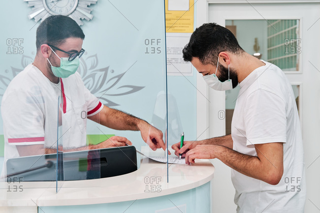 Side view of male doctor in medical uniform and protective mask signing papers while standing at reception desk with receptionist behind glass partition in modern clinic