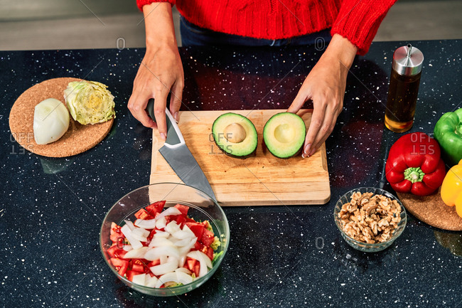 Crop faceless female cook cutting avocado while preparing healthy vegetarian salad in kitchen