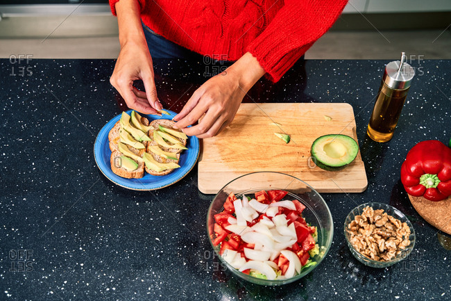 From above of crop unrecognizable female in casual clothes preparing healthy lunch with avocado toast and vegetable salad at home