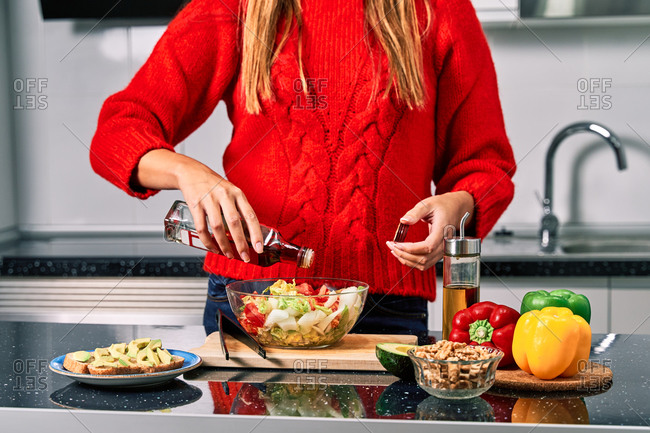 Crop faceless female cook pouring vinegar while preparing healthy vegetarian salad in kitchen