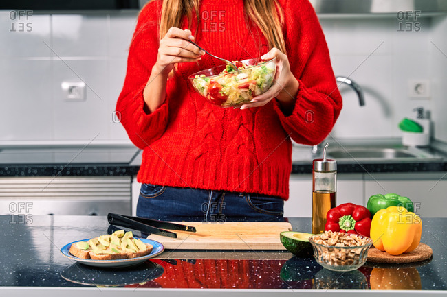 Crop faceless female eating healthy vegetarian salad in kitchen