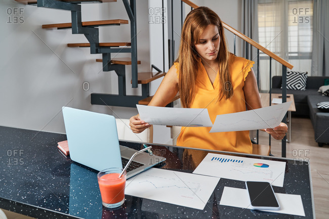 Focused female freelancer sitting at table with laptop at home and analyzing diagrams on paper while working on project remotely