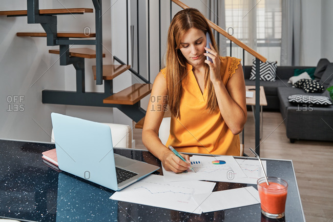 Concentrated female entrepreneur talking on smartphone and taking notes on paper with diagrams while discussing work issues and working remotely
