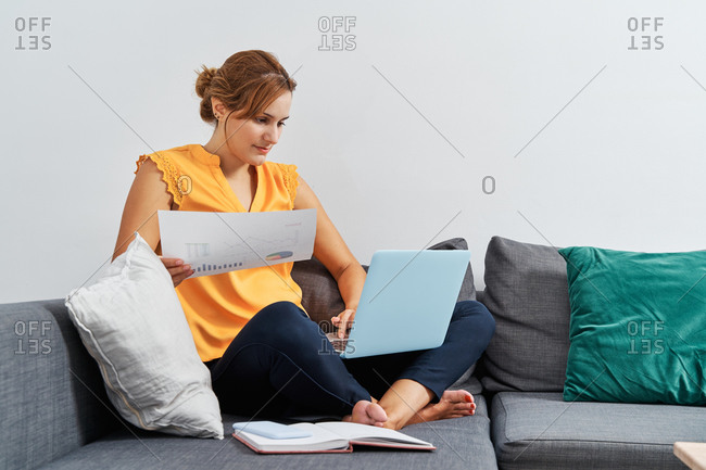 Concentered female entrepreneur sitting on sofa with papers and typing on laptop while preparing report during remote work