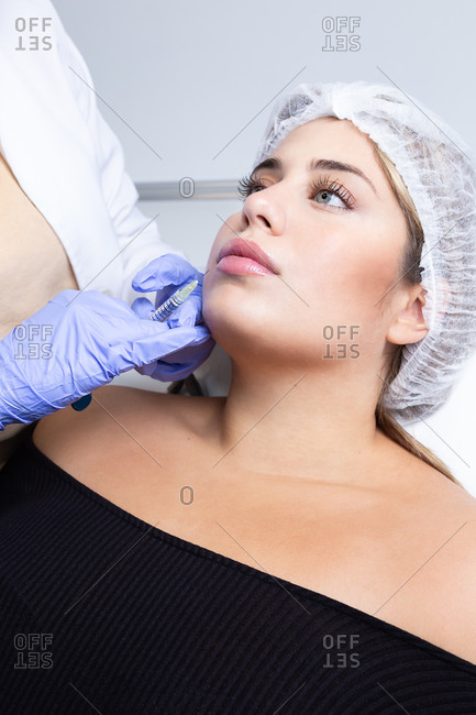 Graceful young female client with long blond hair sitting on medical chair while cut unrecognizable cosmetologist in latex gloves making rejuvenating facial injections procedure in beauty center