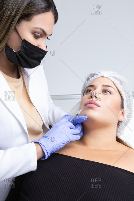 Graceful young female client with long blond hair sitting on medical chair while cosmetologist in latex gloves making rejuvenating facial injections procedure in beauty center