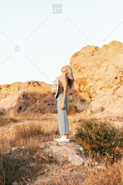 Side view of tranquil topless female in jeans standing in nature and covering breast with hat while enjoying sunset in summer