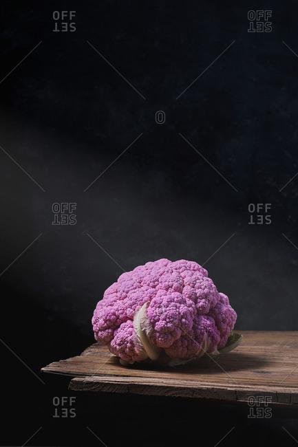 Tasty purple cauliflower placed on wooden table on black background in dark studio