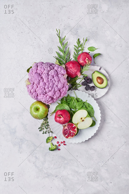 From above of composition of fresh healthy vegetables and fruits placed on white table