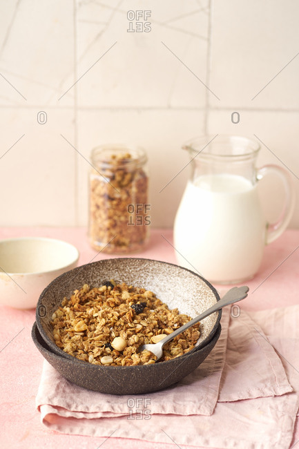 A bowl of granola with nuts, honey and oats served with milk
