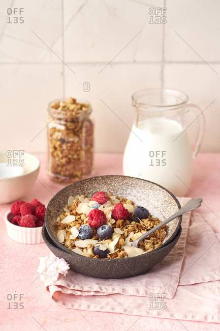 A bowl of granola with nuts and oats served with berries and milk