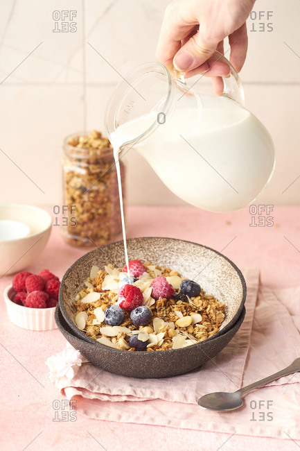 Hand with a jug pouring milk to granola with berries