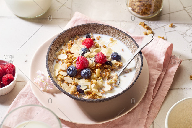 Flat lay with a bowl of granola with nuts and oats served with berries and milk