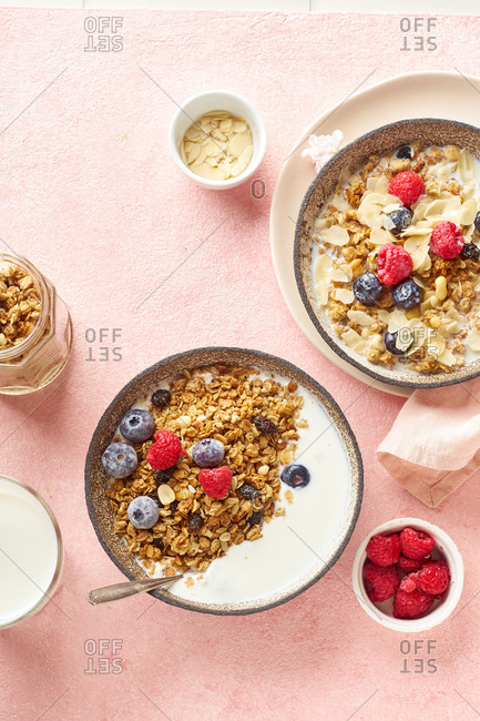 Top view of tasty breakfast with granola, berries and milk on pink background
