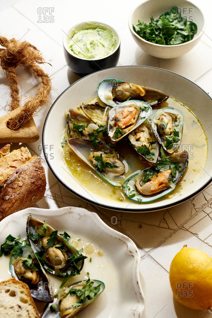 Cooked kiwi green mussels with wine, garlic and parsley served with baguette and butter with herbs