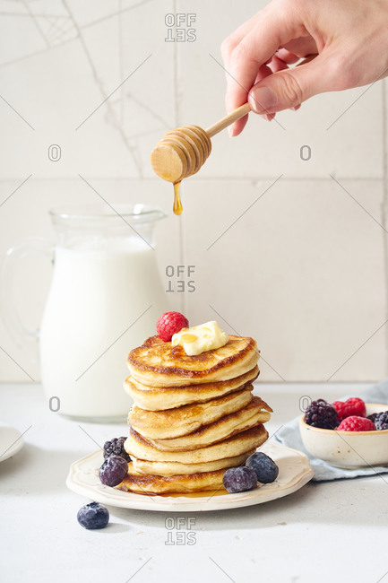 Pouring honey on a stack of fluffy breakfast pancakes with berries and butter