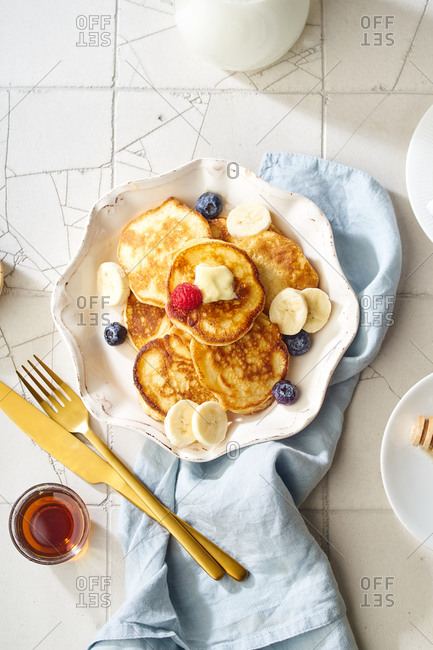 Top view of a plate with fluffy breakfast pancakes with maple syrup and berries