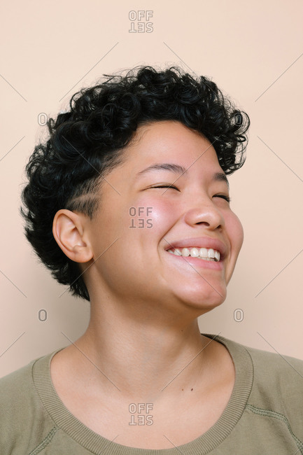 Portrait of young Latina woman with closed Asian eyes smiling, isolated vertical photo, beige background