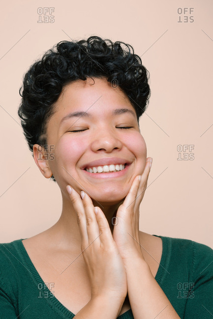 Young Latina woman smiling and touching her face with her hands. Closed eyes. Isolated vertical photo, beige background