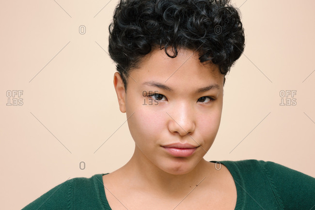 Young Latina woman looking at the camera with her Asian eyes, isolated horizontal photo, beige background