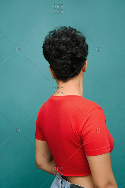 Young Latina woman on her back with a red t-shirt , isolated vertical photo, tidewater green background