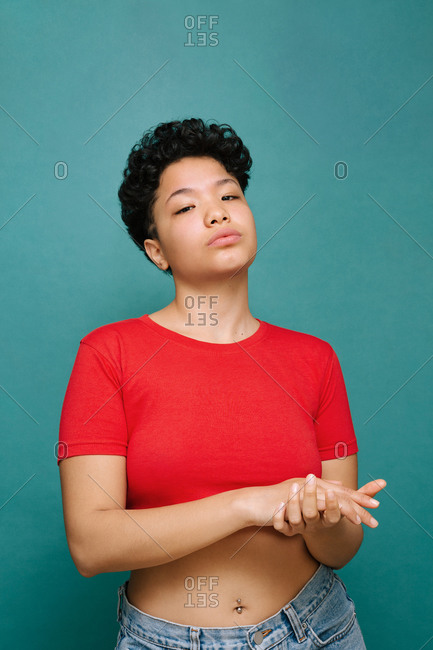 Young Latina woman holding her own hands with a red t-shirt, media shot, isolated vertical photo, tidewater green background