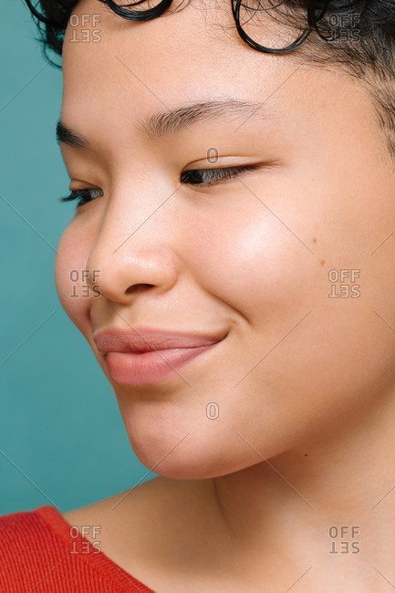 Portrait of young Latina woman with Asian eyes looking to the side, close-up, isolated vertical photo, tidewater green background