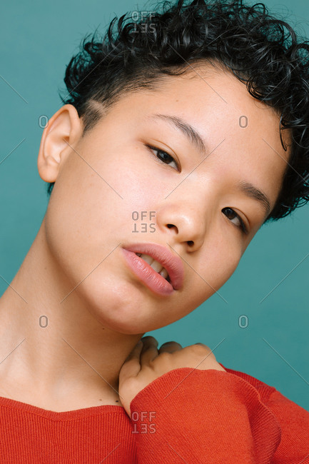 Portrait of young woman with her head bowed and hand on her shoulder, isolated vertical photo, tidewater green background