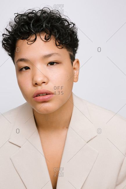 Young Latina woman wearing a beige blazer. Isolated vertical photo, white background