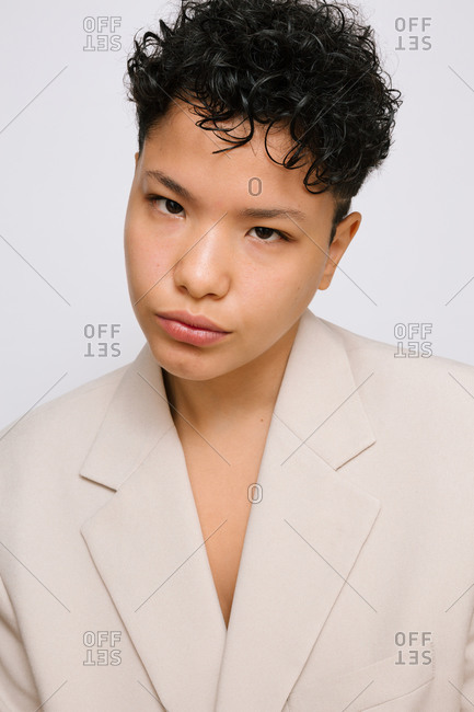 Young Latina woman with Asian eyes wearing a beige blazer, isolated vertical photo, white background
